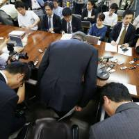 Display of remorse: Deputy President Toshitsugu Okabe of Mizuho Financial Group (center) and other executives make an apologetic gesture Friday in Tokyo. | KYODO