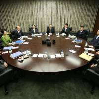 Status quo: Bank of Japan Gov. Haruhiko Kuroda (center) and other members of the BOJ Policy Board begin the second day of their monetary policy meeting Friday morning in Tokyo. They ended the session by keeping the current ultra-loose monetary policy in place. | POOL/KYODO