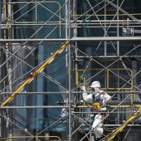 High and dry: A Tokyo Electric Power Co. employee in protective radiation suit and mask climbs scaffolding at the site of the ALPS multi-nuclide removal facility at the Fukushima No. 1 nuclear plant in March. | BLOOMBERG