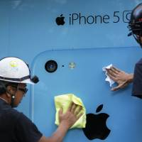 High hopes: Workers prepare a window display for the iPhone 5C outside an NTT DoCoMo store in Tokyo on Sept. 20. | BLOOMBERG