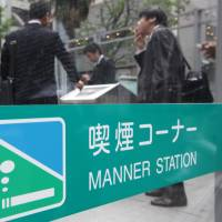 Boxed in: People smoke at a 'manner station' — an invented term for a smoking space — in Tokyo. Japan Tobacco Inc. plans to expand its range of smokeless tobacco products as consumers demand alternatives. | BLOOMBERG