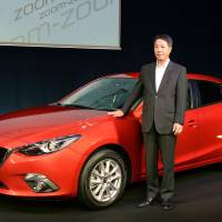 Newcomer: Mazda Motor Corp. President Masamichi Kogai stands by the hybrid version of the Axela compact in Tokyo on Wednesday. | KYODO