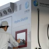 Fueling a dream: Employees of Taiyo Nippon Sanso Corp. operate a hydrogen station in Tokyo during a demonstration Thursday. | BLOOMBERG