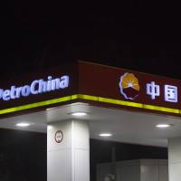 The logo of Petrochina Co. is illuminated at one of its gas stations in Hong Kong. | BLOOMBERG