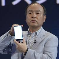 Clash of the titans: Masayoshi Son, chairman and CEO of SoftBank Corp., introduces the Aquos Xx302SH smartphone in Tokyo on Sept. 30. | BLOOMBERG