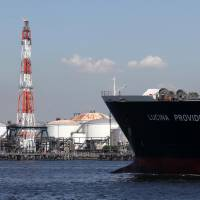Staking their claim: A tanker carrying liquefied petroleum gas sails past an oil refinery in an industrial section of Kawasaki in September 2012. | BLOOMBERG