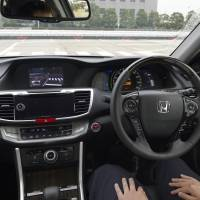 Look mom, no hands: An employee 'drives' a Honda Accord hybrid with an automatic driving system at the ITS World Congress Tokyo 2013 on Tuesday. | BLOOMBERG