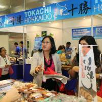 Foodies: Visitors ask questions at the Hokkaido booth of the 'Oishii Japan' food exhibition that opened Thursday in Singapore.   KYODO
