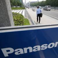 Let the chips fall: A man walks past a Panasonic Corp. sign at the company's headquarters in Kadoma, Osaka Prefecture, on July 31. | BLOOMBERG