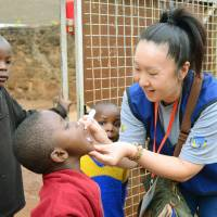 Summer field trip:  Yoko Endo, a nursing assistant from Osaka, administers a polio vaccine to a child in Nairobi. | KYODO