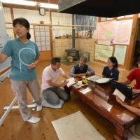 For the kids: Instructors overseeing an exchange program in Toyone, Aichi Prefecture, meet in the Seizanso dorm. Some 100 children from urban areas have lived in Seizanso (below) since 1985 to experience rural life. | CHUNICHI SHIMBUN