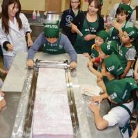 Roll with it: Elementary school students and their parents create the world's biggest piece of chewing gum Saturday in Sapporo, setting a new Guinness world record. | KYODO