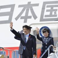 On three: Prime Minister Shinzo Abe and his wife, Akie, wave to well-wishers as they leave for Bali, Indonesia, from Kansai International Airport on Sunday. | KYODO