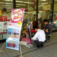 Added convenience: A father with a baby in Minato Ward signs up for the Smart Kitchen home delivery service targeting working parents that convenience store Lawson Inc. introduced in January. | MAMI MARUKO