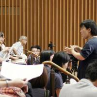 Helping hands: A sign language expert interprets for people with hearing disabilities during a session of the Tottori Prefectural Assembly on Tuesday. | KYODO