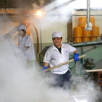 Brewers sterilize tools with hot water on Sept. 3 in Nagaoka, Niigata Prefecture, to prepare for sake production this month. | KYODO
