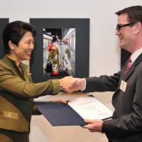 Picturesque: Princess Hisako awards the Prince Takamado Memorial Prize to Ciaran Chestnutt of the Australian Embassy during the opening of the 'Japan Through Diplomats' Eyes' photo exhibition at Roppongi Hills in Tokyo on Thursday. | YOSHIAKI MIURA