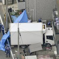 Assault with a deadly weapon: Police inspect a house rammed by a man's truck Thursday in Kawaguchi, Saitama Prefecture. | KYODO