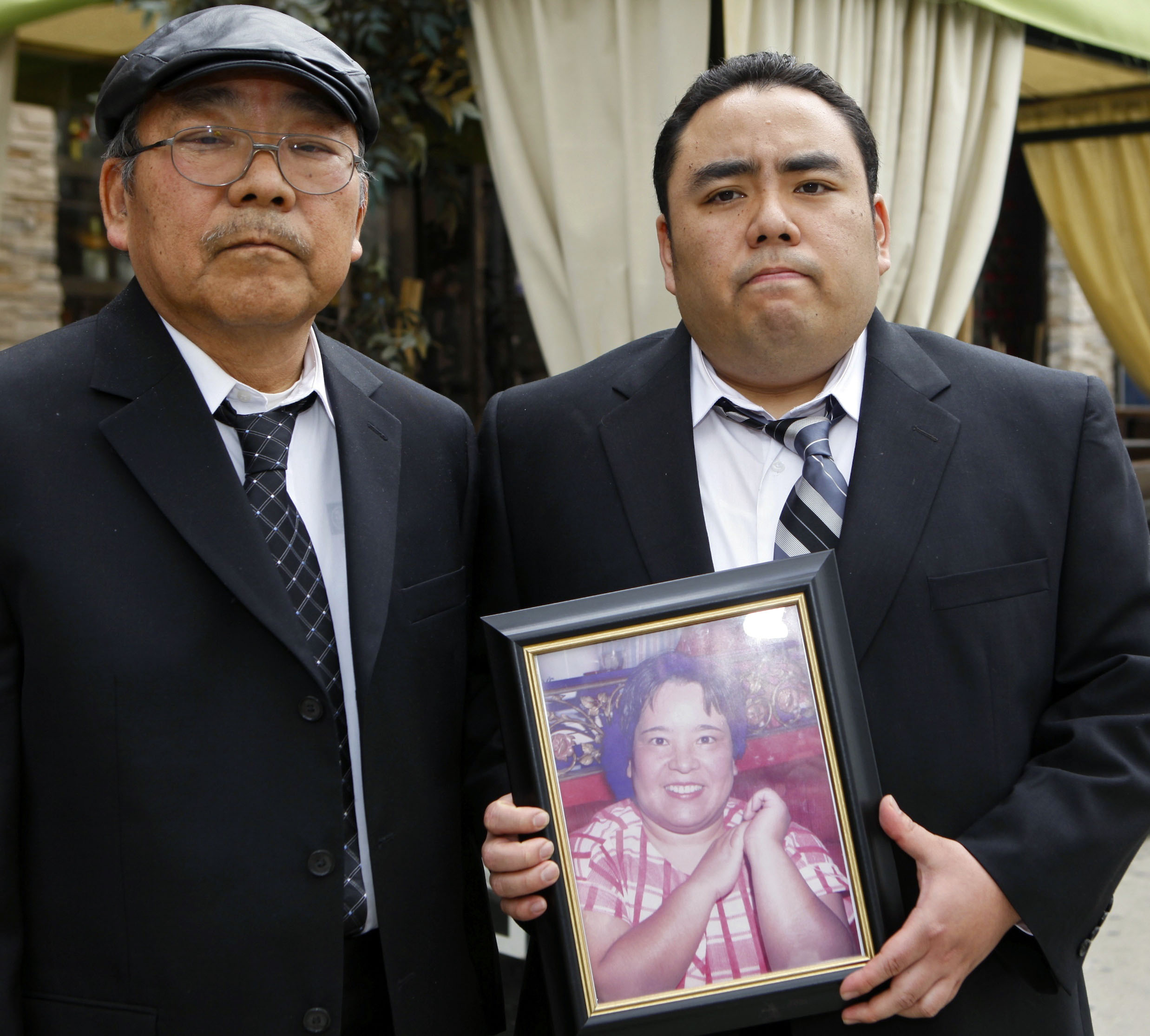 Crash loss: Jeffrey Uno holds a photo of his late mother, Noriko, as his father, Peter, looks on in February 2010. | AP
