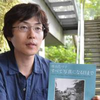 Only memories: Masashi Kohara, a researcher at the Izu Photo Museum in Shizuoka Prefecture, talks about the work of amateur photographer Tazuko Masuyama. As her life work, Masuyama, who died in 2006 at age 88, documented through photos a village that was eventually submerged by the Tokuyama Dam project in Gifu Prefecture. | CHUNICHI SHIMBUN