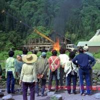 Villagers watch as their houses are demolished and burned before the dam was built. | CHUNICHI SHIMBUN