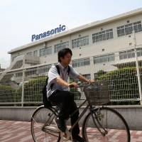 Picking up speed: A man rides past Panasonic's headquarters in Kadoma, Osaka Prefecture, on July 31. | BLOOMBERG