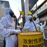 Sounding a warning: Protestors in radiation suits bang a drum during an antinuclear demonstration in front of Tokyo Electric Power Co. in Tokyo on Sunday. | AFP-JIJI
