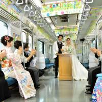 Tying the loop: Guests applaud newlyweds Nobuhiko Suzuki and Sayaka Tsuchiya during their wedding ceremony aboard a specially chartered Yamanote Line train in Tokyo on Monday. | KYODO