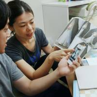 Details, details: Koki Fukumoto and his fiancee discuss preparations for their wedding while looking at a picture on a free smartphone app created by Novarese Inc. | KYODO