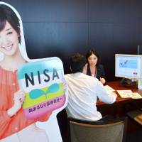 Taking a chance: A brokerage official in Tokyo explains the Nippon Individual Savings Account to a prospective client. | KYODO