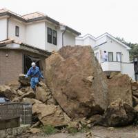 Crushing: A huge boulder lies in the road after ramming into a house in Kamakura, Kanagawa Prefecture, in a landslide caused by Typhoon Wipha on Wednesday. Right: Trees lie flattened on Izu-Oshima Island, south of Tokyo, the same day. | KYODO