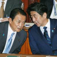 Don't panic: Prime Minister Shinzo Abe (right) chats with Finance Minister Taro Aso during a Lower House session Wednesday. Abe told the session the mounting accumulation of radioactive water at the crippled Fukushima No. 1 nuclear plant is a situation that is 'under control.'   KYODO