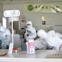 At what cost?: Toho Bank employees, in radiation suits, retrieve cash and documents left in its branch in Okuma, Fukushima Prefecture, within the 20-km no-go zone from the Fukushima No. 1 plant in April 2011. A government agency said Wednesday it will take up to 31 years to recover ¥5 trillion in aid for Tokyo Electric Power Co. for compensation related to the nuclear disaster. | KYODO