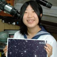 Star pupil: Akiko Takahashi holds a picture of an asteroid that she and two friends discovered in 2009, during an interview at her high school in Kanagawa Prefecture in August. | KYODO