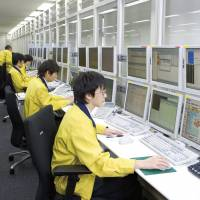 Lines of communication: Operators work at Tokyo's Network Total Operation Center, where about 20 interpreters deal with inquiries in foreign languages. | COURTESY OF NEC NETWORKS & SYSTEM INTEGRATION CORP.