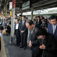 Remembering a hero: Lee Sung-dae and Shin Yoon-chan (right), pray Thursday on the platform at JR Shin-Okubo Station in Tokyo where their son, Lee Su-hyon, died 12 years ago trying to save a Japanese man who had fallen onto the tracks. | YOSHIAKI MIURA