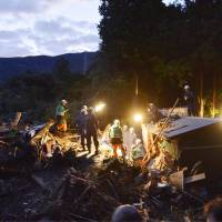 Holding onto hope: Rescuers continue to search early Thursday for survivors in debris left by a typhoon-triggered landslide on Izu-Oshima Island. | KYODO