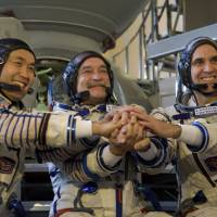 In it together: Space-bound (from left) Japanese astronaut Koichi Wakata, cosmonaut Mikhail Tyurin and NASA astronaut Rick Mastracchio prepare for their final preflight practical examination in a mockup of a Soyuz TMA spacecraft at Russia's space training center in Star City, outside Moscow, on Thursday. | AP