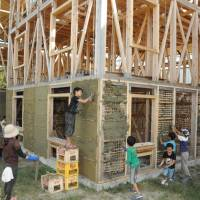 Hands-on training: Kids help build the soil-and-bamboo wall of the Home-for-all guest house at Aioiyama Tokurinji Temple in Tenpaku Ward, Nagoya, earlier this month. | CHUNICHI SHIMBUN