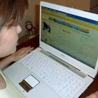 New style: A woman checks for clothing items being sold to the highest bidder on an online auction site. | KYODO