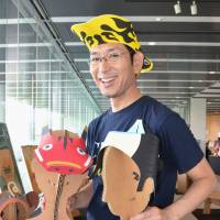 Get happy: Headdress creator Chappy Okamoto shows off some of the 'kaburimono' items he has created. | KYODO