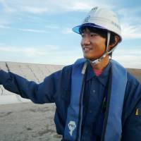 Rebuilding an industry: Kazuki Kosaka, a 22-year-old employee at contractor Atami Kensetsu, works at a construction site in Sendai in September. | KYODO