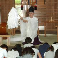Forward-looking: Mitsunobu Okada, chief priest of Sugimori Shrine in Higashihiroshima, Hiroshima Prefecture, holds a purification ceremony attended by children on Sept. 8. | KYODO