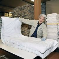 Happy helper: An elderly worker registered with Koreisha cleans bedding at a company he was dispatched to. | KYODO
