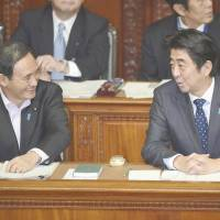 On the lighter side: Prime Minister Shinzo Abe chats pleasantly with Chief Cabinet Secretary Yoshihide Suga during the Lower House plenary session Friday. | KYODO
