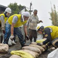 Protective action: Volunteers pile sandbags in front of a building on Oshima Island on Thursday afternoon before the arrival of Typhoon Francisco. | KYODO