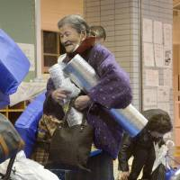 An elderly woman is relieved and leaves a shelter on Saturday evening after the evacuation order and advisory were lifted.   KYODO