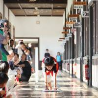 Cleanup: A child pushes a duster along a hallway during a cleaning race held in Seiyo, Ehime Prefecture, on Friday. | KYODO