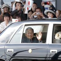 Public display: Emperor Akihito waves to the public as his car arrives at Kumamoto airport Monday afternoon. | KYODO