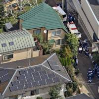 Evidence hunt: Police investigators gather in front of the home of murder victim Saaya Suzuki, an 18-year-old high school girl, Wednesday morning in the western Tokyo suburb of Mitaka.  | KYODO